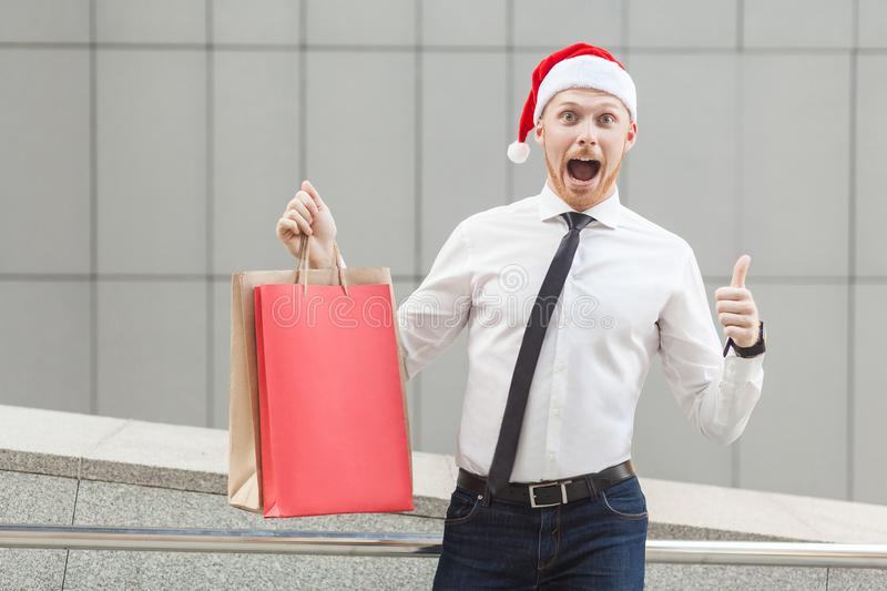 Young adult ginger businessman thumbs up and looking at camera with shocked face. stock image