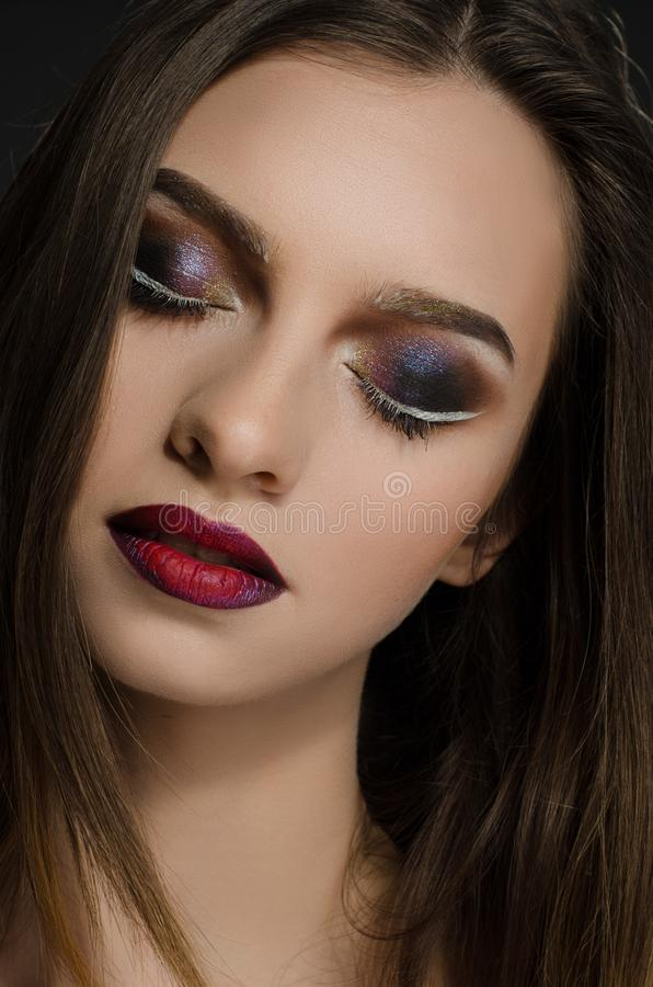 Young adult girl with beautiful evening makeup on a black background royalty free stock images
