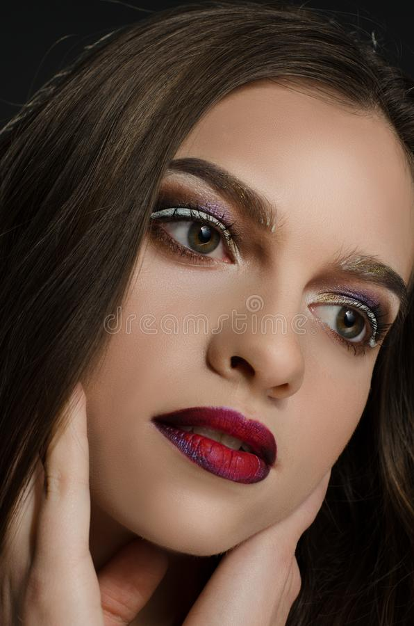 Young adult girl with beautiful evening makeup on a black background stock image