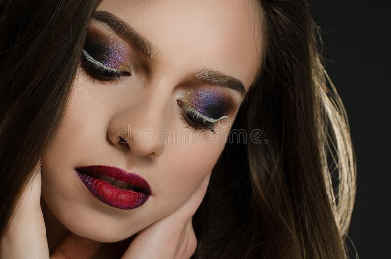 Young adult girl with beautiful evening makeup on a black background royalty free stock photography