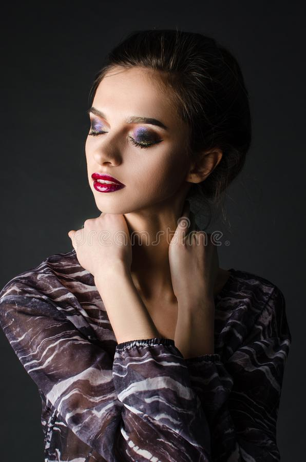 Young adult girl with beautiful evening makeup on a black background royalty free stock image