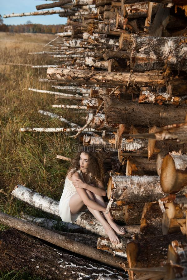 A young adult girl clapped on a birch log royalty free stock photo