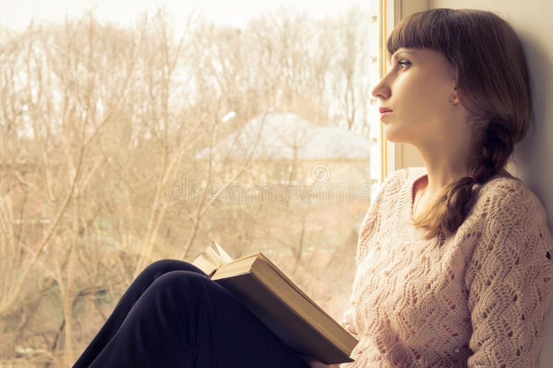 Young adult girl reading book near the window. Warm toned image stock photography