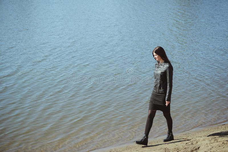 Young adult girl walking alone on sea sand beach stock images