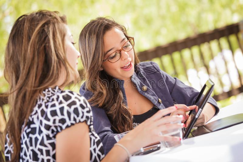 Young Adult Girlfriends Using Their Tablet Computer. Expressive Young Adult Girlfriends Using Their Computer Electronics Outdoors royalty free stock photography
