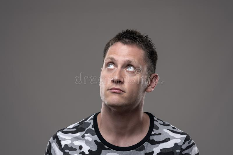 Young adult handsome man looking up thoughtfully thinking for a solution stock image