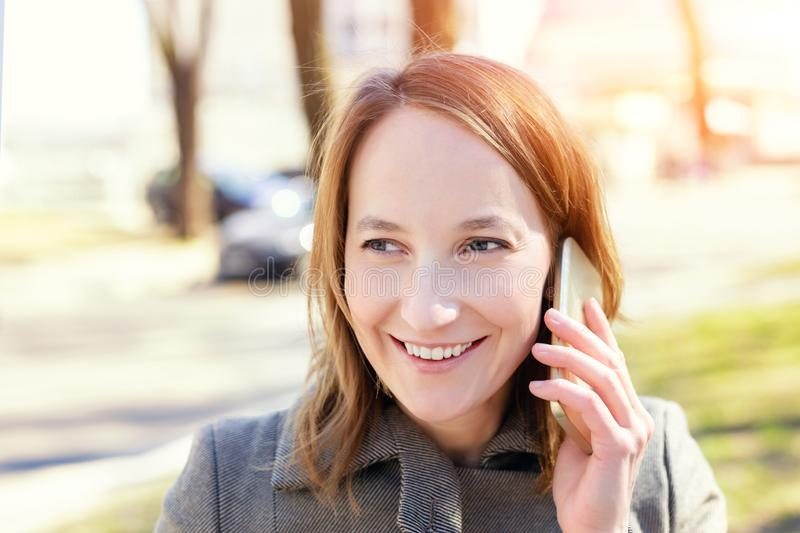 Young adult happy caucasian wooman smiling while speaking smartphone outdoors stock photos