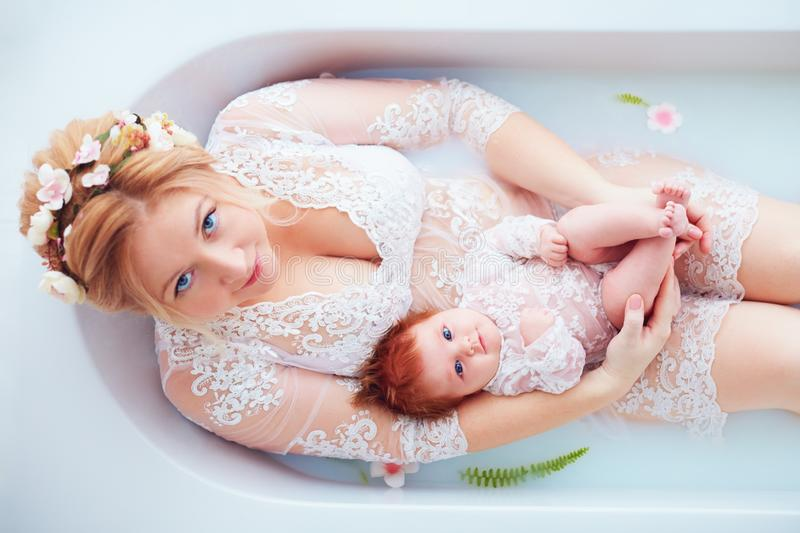 Young happy mother with newborn baby girl, daughter in floral milk bath, family look outfit stock photography