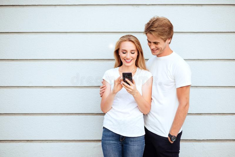 Young adult hipsters. boy and girl in white T-shirts smile and making selfie. royalty free stock photography