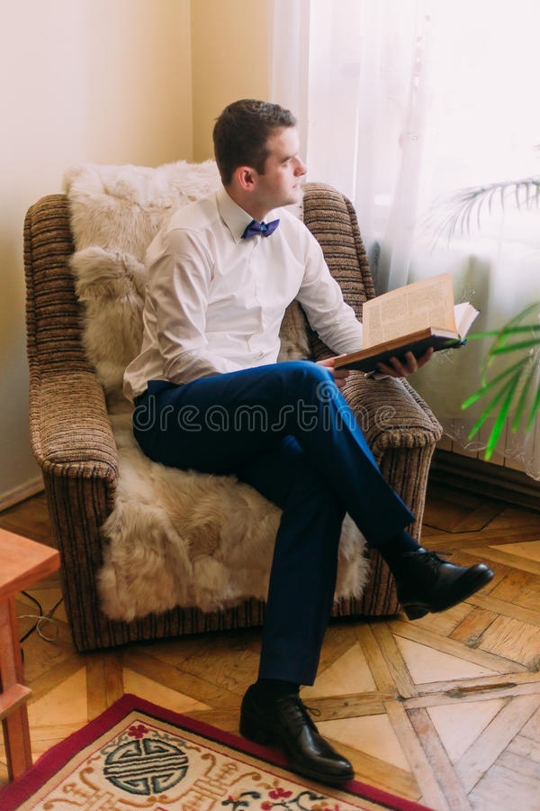 Young adult male in blue suit and white shirt looking off into the distance with a book on his hand.  stock photos