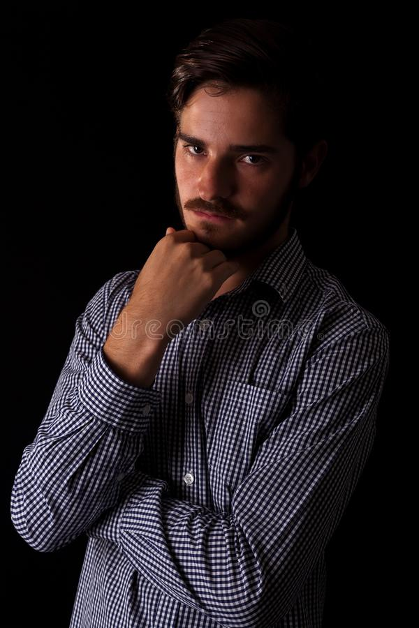 Young adult male looking sinister or contemplative. Color expressive dramatic effect, dark and moody series. Young adult male looking sinister or contemplative stock photo