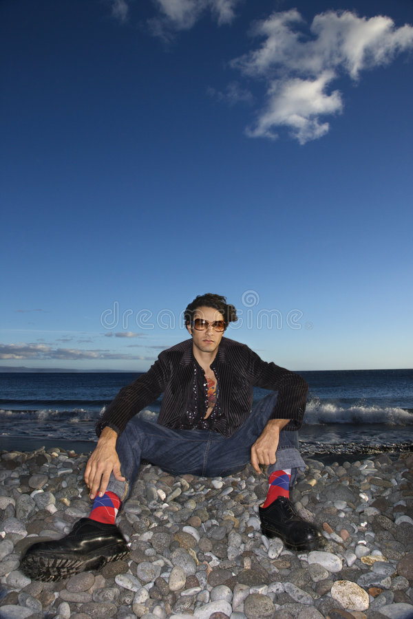 Young adult male sitting on rocky beach. stock photos
