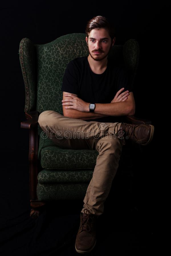Young adult male looking sinister or contemplative. Color expressive dramatic effect, dark and moody series. Young adult male sitting in vintage wingback chair stock photography
