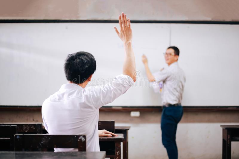 Young adult male student raising hands up in the air to ask questions from another male teacher. royalty free stock image
