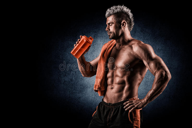 Young adult man drinking protein shake in gym. Black background. stock photos