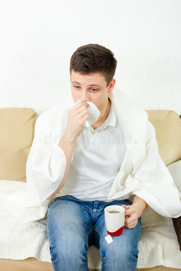 Young adult man feeling sick. Male model having severe cold. Sneezing and cleaning nose with tissue paper while holding cup of hot tea. Concept photo, sickness stock images