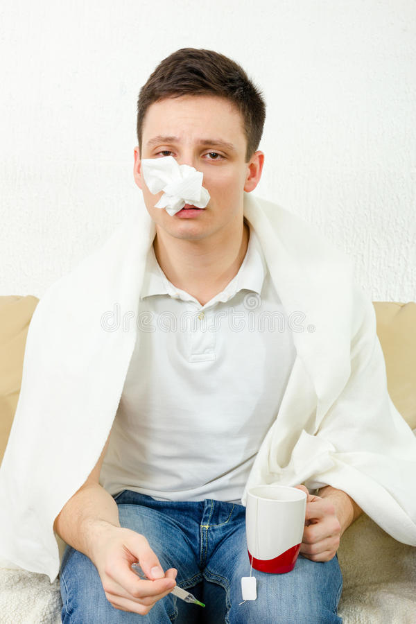 Young adult man get caught by virus epidemic. Devastated and in misery covered with blanket sitting on couch and measuring body themperature. Tissue full of stock photos