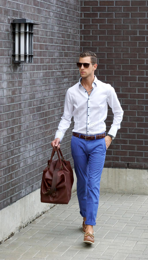 Young Adult Man Holding A Duffle Bag Walking. Young adult male wearing sunglasses and carrying an overnight bag stock photo