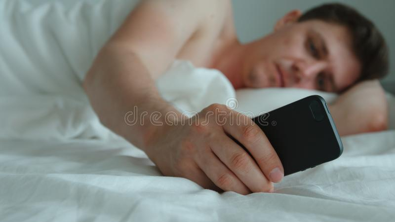 Young adult man lies on a bed and uses phone royalty free stock photos