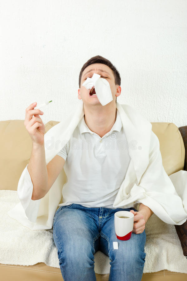 Young adult man suffering flu. Holding thermometer and tea in hand and has tissue paper on his nose, sneezing. Looking sad and desperate to temperature results stock photos