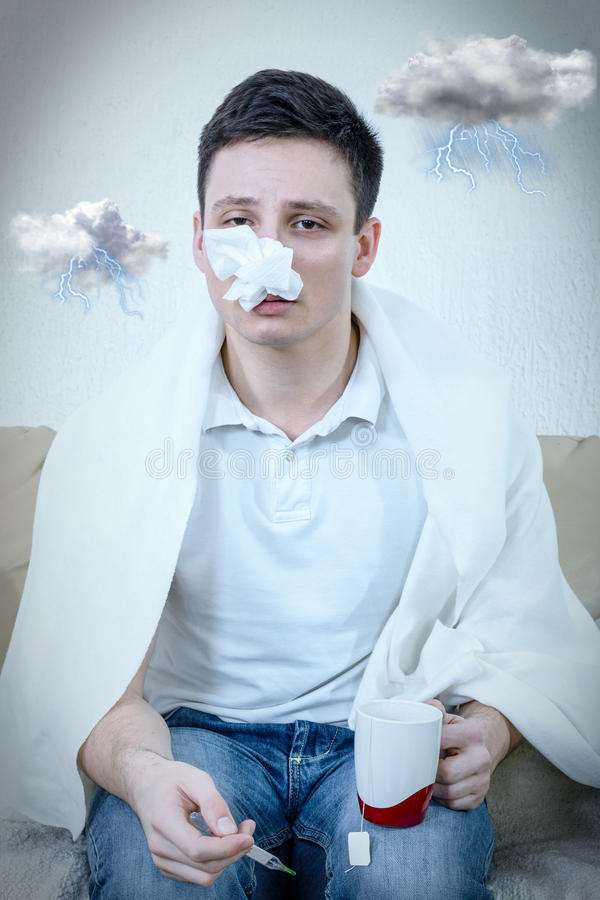 Young adult man suffering pollen allergy. Man suffering from pollen allergy, dark storm clouds around his head. Holding thermometer and a cup of tea. Kleenex or stock photos