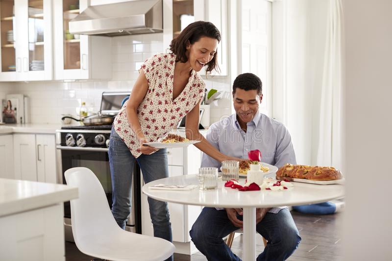 Young adult man sitting at the table in the kitchen is served a romantic meal by his partner, selective focus stock images