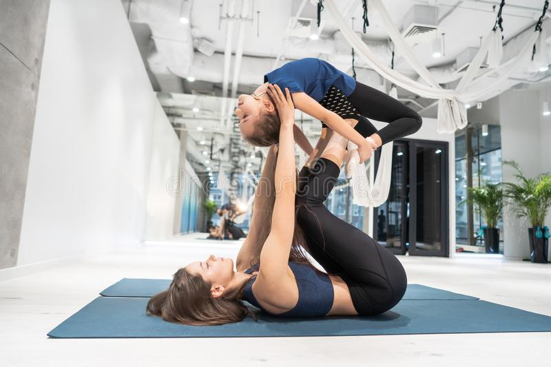 Young adult mother doing fitness with her little daughter royalty free stock photo