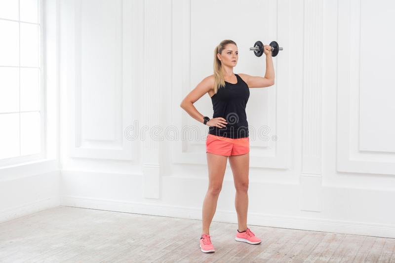 Young adult motivation athletic beautiful bodybuilder woman in pink shorts and black top standing, holding dumbells doing exercise. For arms at the gym with royalty free stock image