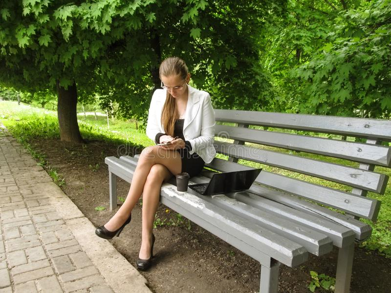 Young adult nice girl in glasses wipes her mobile by cloth, sitting on a bench with a laptop and coffee. Businesswoman in a suit royalty free stock photography