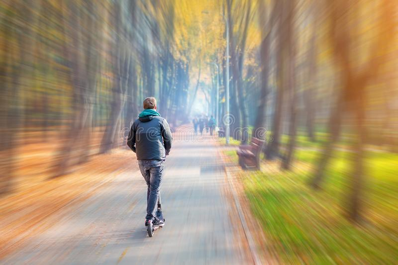 Young adult person riding modern electric scooter along beautiful colorful autumn city park. Man driving gadget vehicle through royalty free stock images
