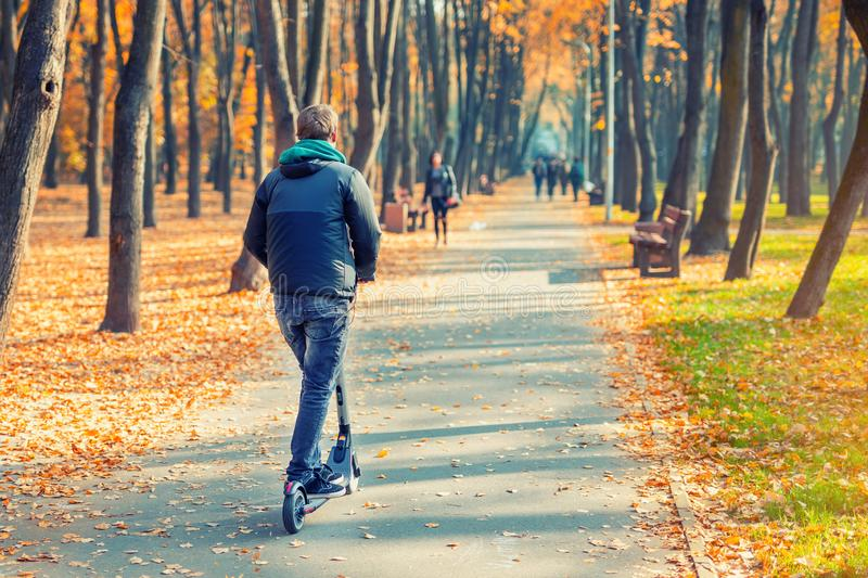 Young adult person riding modern electric scooter along beautiful colorful autumn city park. Man driving gadget vehicle through royalty free stock photos
