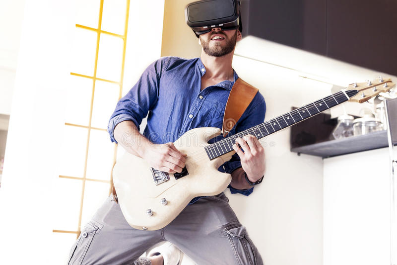 Young adult playing guitar at home using viewer. For augmented reality stock image