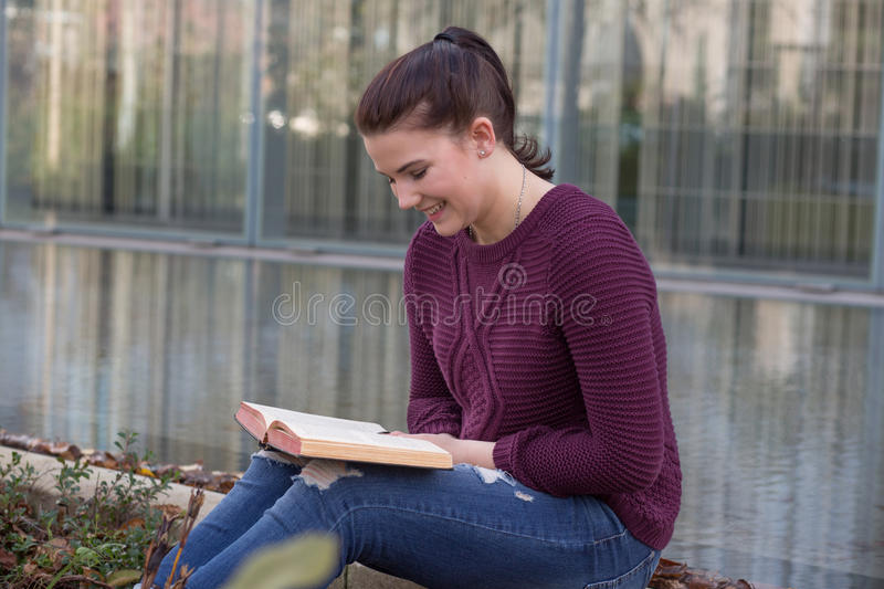 Young adult reading book stock images