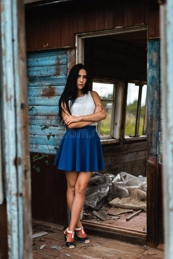Young adult seductive brunette in blue skirt and white shirt posing in rustic house outdoors. Young adult seductive brunette in blue skirt and white shirt posing stock images