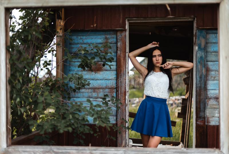 Young adult seductive brunette in blue skirt and white shirt posing in rustic house outdoors. Young adult seductive brunette in blue skirt and white shirt posing royalty free stock photos