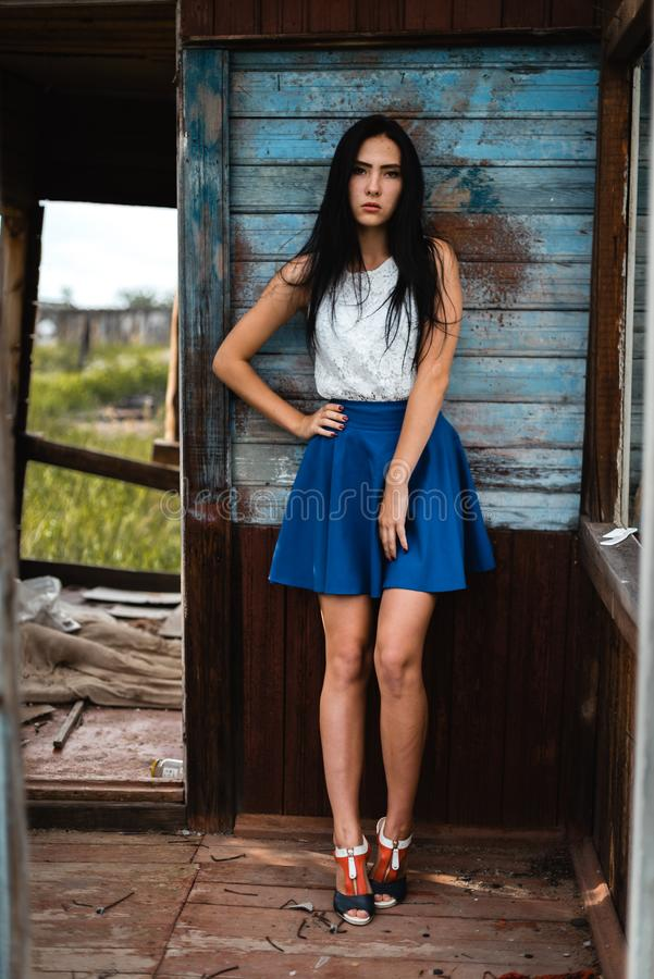 Young adult seductive brunette in blue skirt and white shirt posing in rustic house outdoors. Young adult seductive brunette in blue skirt and white shirt posing royalty free stock photo