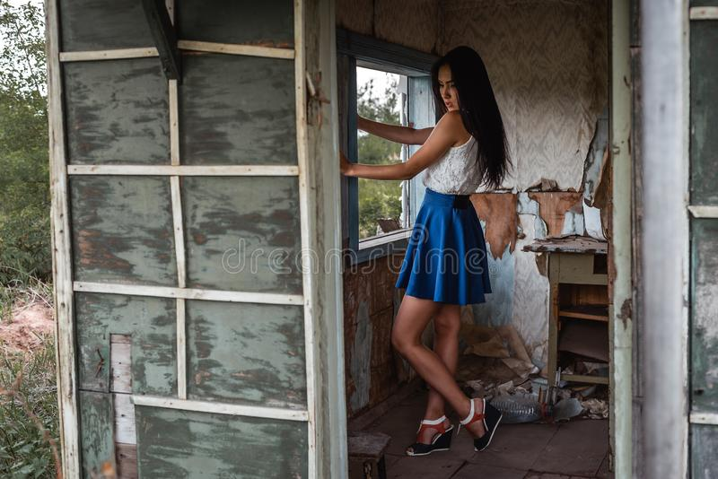 Young adult seductive brunette in blue skirt and white shirt posing in rustic house outdoors. Young adult seductive brunette in blue skirt and white shirt posing stock photos