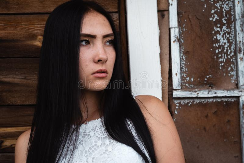 Young adult seductive brunette in white shirt posing in rustic house outdoors royalty free stock images