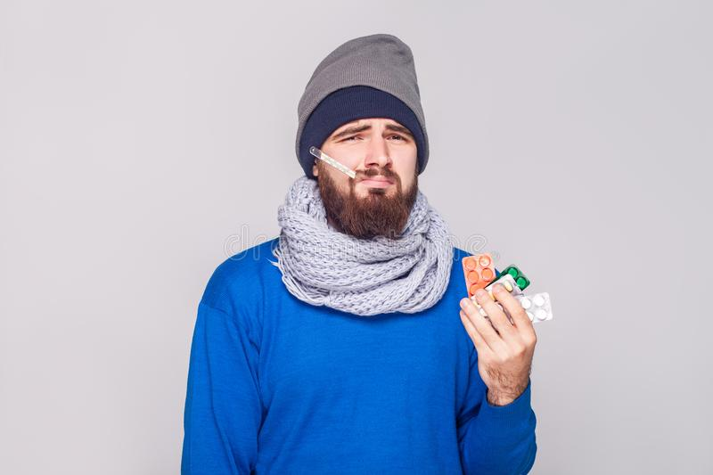 Young adult sick man have temperature, holding many pills. Studio shot, isolated on gray background stock images
