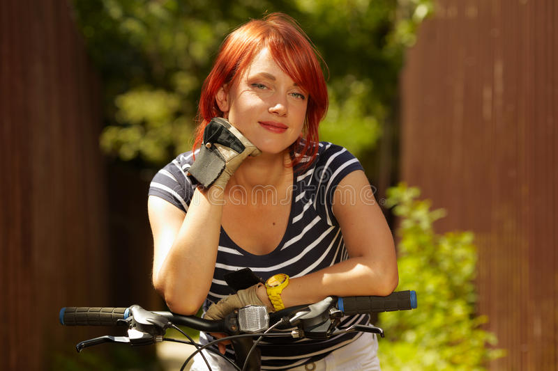 Young adult smiling biker woman on mounting bike royalty free stock photography