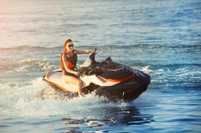 Young adult sporty caucasian woman riding jet ski in ocean blue water at warm evening sunset. Beach extreme sport activities and stock photography