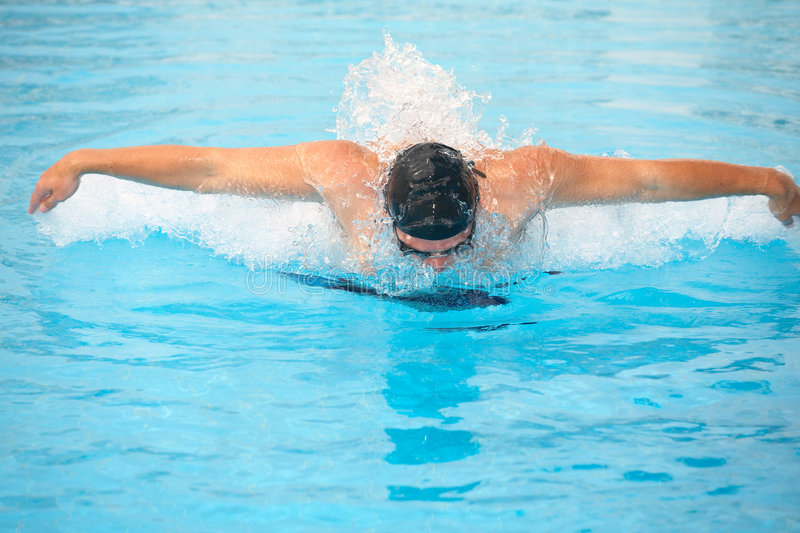 Young adult swimmer. Healthy young adult male aquatic athlete. Professional swimmer in blue water stock photography