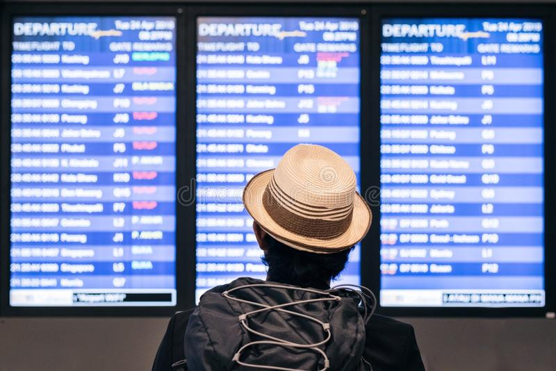 Young adult tourist traveler backpaker looking at airport flight schedule timetable on the screen royalty free stock photos