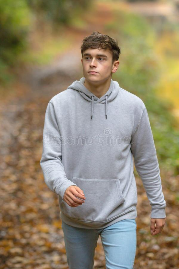 Young adult walking outside. Teenage young adult walking along a woodland path on an autumn day stock photos