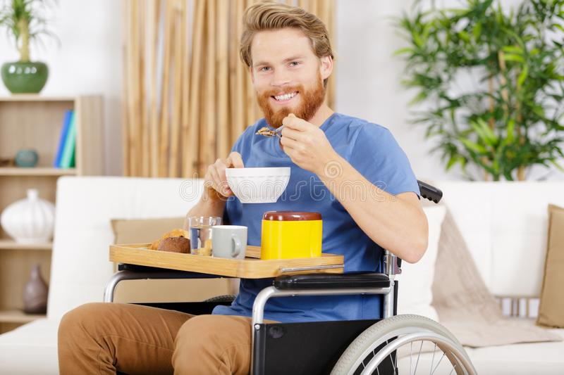 Young adult in wheelchair enjoying bowl cereal royalty free stock images