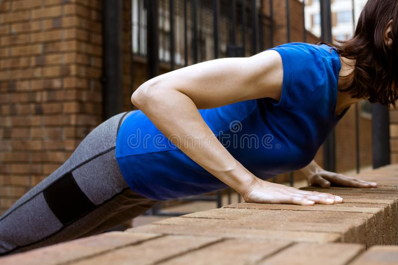 Young adult white woman doing bench push ups outside. Selective focus stock photo