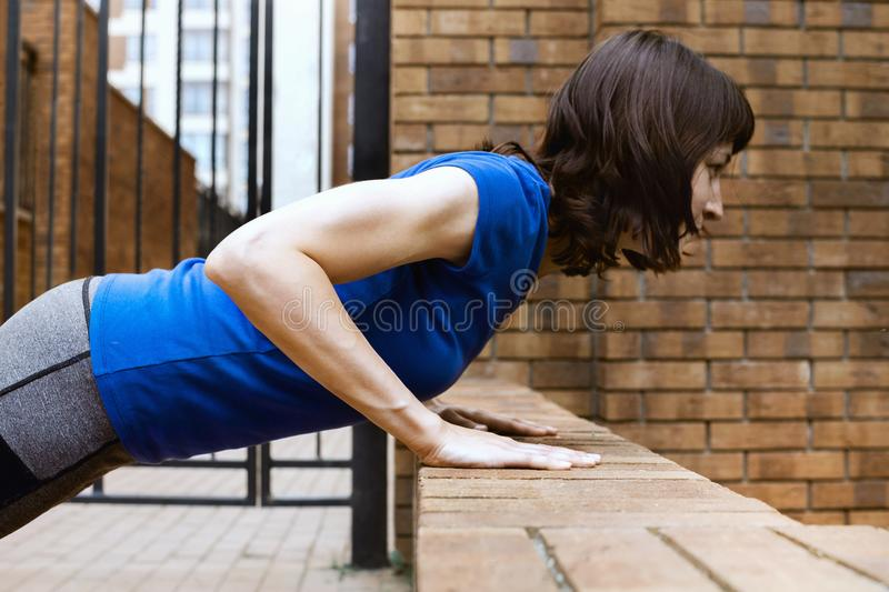 Young adult white woman doing bench push ups outside. Selective focus royalty free stock photo