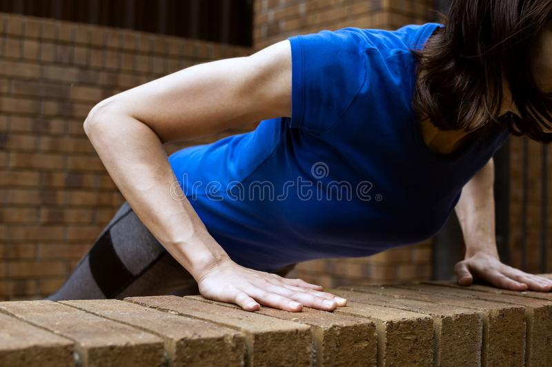 Young adult white woman doing bench push ups outside. Selective focus stock photos