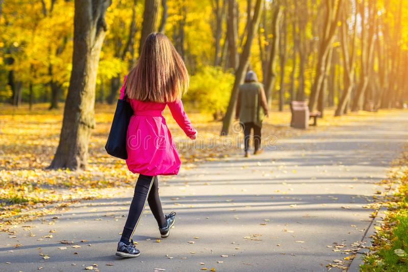 Young adult woman in bright casual coat walking along beautiful golden colored autumn park alley. Happy attractive sporty girl in stock images