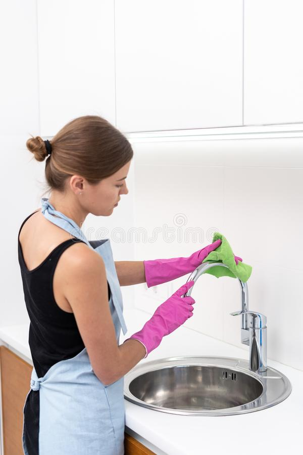 Young adult woman cleaning sink at kitchen stock images